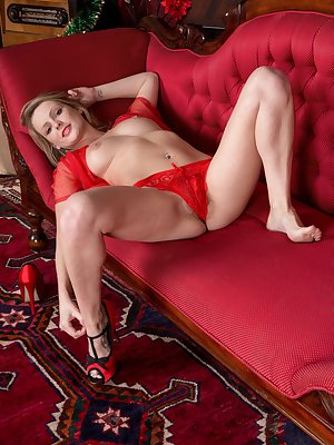 It is a festive New Year, and Vanessa Scott has her finest blouse and skirt on. The red lingerie underneath comes off and she lays on her red couch. She poses nude and smiles showing her hairy pussy.