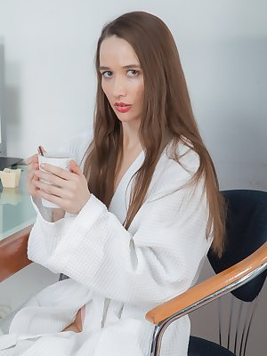 Rose Nore enjoys tea and is sipping some in her white robe. The robe and pink lingerie come off afterwards and she sits naked. She climbs on her table, spreads her legs, and exposes her hairy bush.