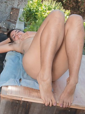 Katie Z is on her patio in her pink blouse and denim jumper. She undresses outdoors and shows off her hairy pits and pussy. She even has hairy legs and she gets on her wooden table to show it all.