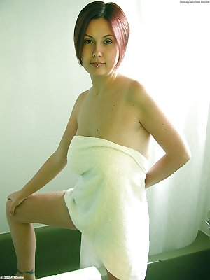 Amateur Asian model Gwen exposing hooters and tattoos in bathroom