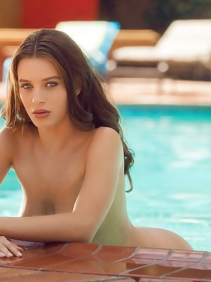 Solo model Lana Rhoades peels off her beach attire next to a swimming pool
