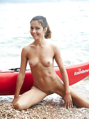 Butt naked babe Sati poses in the kayak on the wild beach