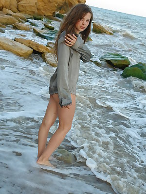 Nice teen girl Petra E removes her shirt after wading out into the ocean
