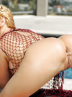 Fishnet attired Euro babe Sandy showing off wet MILF tits in swimming pool