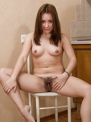 """Leona is pretty in pink, and her pink dress and pink lingerie show it. She slowly undresses and shows off her 5'2"""" petite Russian all-natural figure. Her hairy pussy is delightful as is her cute body."""