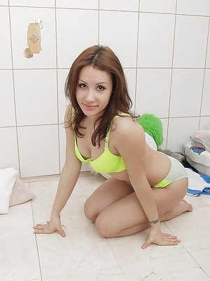 Alone in her bathroom, Leona strips out of her lime green lingerie to get naked. Across the bathroom floor, she spreads her legs and gives us all a full view of her hairy pussy and bush.
