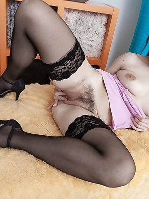 In her pink top and black stockings, Corazon Del Angel lays on her bed very inviting. She shows off her body and shows us her hairy pussy midway in. She opens her legs for a full view of a hairy pussy too.