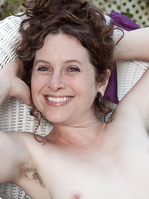 Fiona M is in her bikini outdoors and shows off her hairy pits right off the bat. As she strips naked, she climbs on her white chair and shows off her hot all-natural body which features her hairy pussy.