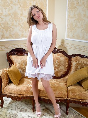 Hairy girl Fina is a sexy blonde babe wearing a sexy white dress. She sits on the couch and slowly strips out of her dress and panties and shows off her long sexy legs and her hairy pussy.