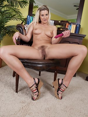 Melania is a sexy blonde babe wearing a blue jean skirt as she stands in her study and slowly strips out of her clothes until she is naked and shows off her warm hairy pussy and round perky tits.