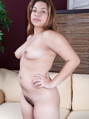 Daisy Leon sits on the couch but quickly moves to the floor to stretch out of her jeans revealing her beautiful all natural hairy pussy. Watch her as she shows off to the world.