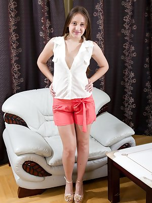Hairy chick Flora is a sexy brunette babe wearing a white blouse with bright red shorts as she stands in her living room. She starts to slowly strips naked and shows off her beautiful hairy pussy.