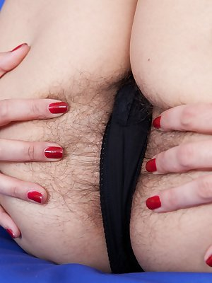 Sitting on the blue couch with rectangular patterned pillows, Vanessa J slowly strips and then inserts her toy in her hairy pussy. Then she rest the vibrator on her huge tits in this hirsute porn.