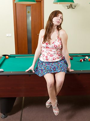 Silviya hops up on the pool table and spreads her hairy legs, barely flashing her pussy hairs poking out from under her white panties before taking them off for a better view.
