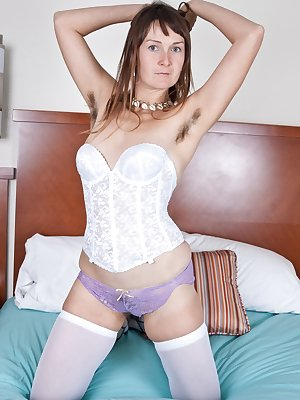 In her white bustier and purple panties, hairy girl Charlotte B doesn't have anyone to be dressed up for but herself, and that's plenty excuse for her. She likes what she sees, and rubs her hairy pussy.