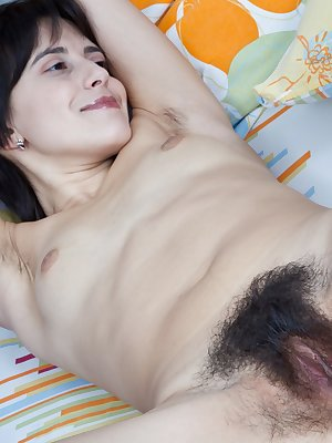 Lanka spends a summer afternoon in bed as she teasingly removes her clothes. Her hairy pussy begins to be visible with her panties still on. As she removes her panties she opens her legs and uses her hands to spread apart the lips to give a perfect shot o