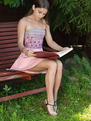 Evelina Darling is outside on her bench reading and taking sexy selfies. She slides off her pink dress and gets turned on. She starts touching her pussy and strokes her hairy bush to orgasm on the bench.