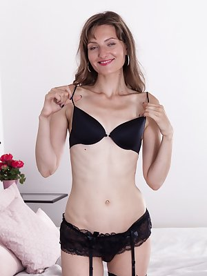 "Lulu is enjoying her black lingerie and modeling away her sexy figure. She strips nude and lays back on her bed. Her 5'8"" body is beautiful, and her hairy pussy that she touches is so inviting."