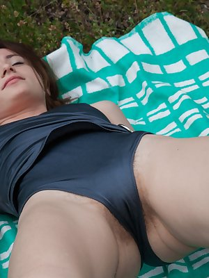 Shaya is enjoying a picnic outdoors and feeling horny. She takes off her blue outfit and lays on her green towel. She packed her dildo and fucks her hairy pussy as she masturbates outdoors today.