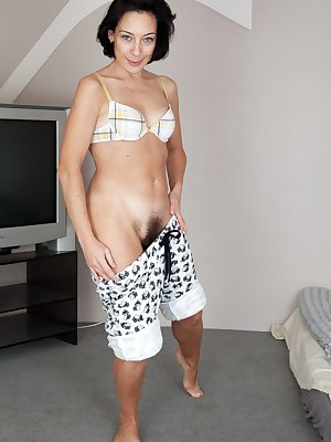 Eva is a sexy brunette with a tone stomach. She pulls down her shorts just a bit to show the top of her pussy hair. Once she gets completely naked she shows her amazingly hairy patch of long pubes.