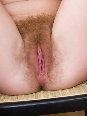 Natural Nomi lays down on the floor and spreads her moist pink hairy pussy with her finger tips while smiling cheekily.