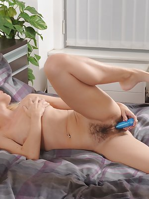 Laying back on her bed with her legs in the air, Lenny thrusts her blue dildo into her moist hairy pink bush.
