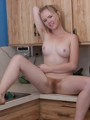 Eve Kisa unveils her beautiful pale body in the kitchen and slides a finger into her warm moist hairy bush.