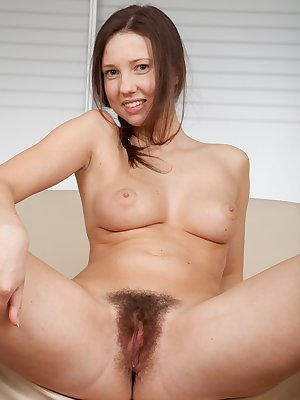 With her bare hairy ass planted firmly back on the couch, Iveta Z opens her creamy thighs and drives fingers deep into her juicy hairy pussy.