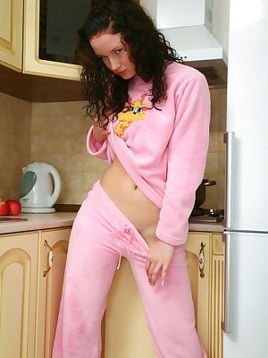 Sexy brunette Kriss is feeling naughty and strips off in the kitchen. Check out her perky tits and tight ass as she mounts the bench top naked.