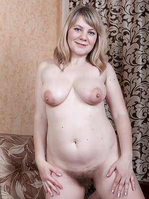 Evlalia is in a beautiful black dress and yellow top and wants to show us her natural body. On her sofa she lays naked showing off her 36C breast and hairy pussy. She touches her pink lips and is hot.