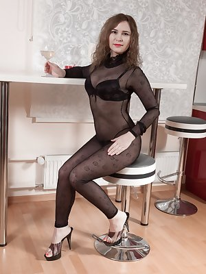 Adelis Shaman is enjoying wine in her black stockings and lingerie and eager to show off her body. She climbs on the table nude, and shows off her very hairy bush. She touches it and has a hot body.