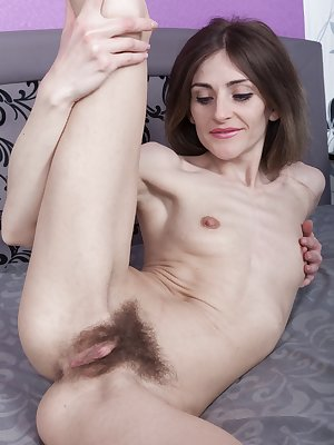Olivia Arden is in blue and black in her purple bedroom and taking off her clothes. She lays back in bed, and shows us her long hair slender body, and then poses with her hairy pussy all exposed.