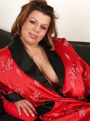 Vanda's gigantic tits are just popping out of her bra and robe. Why not just get them out? Soon enough she bares it all and starts to run her hands through her bush.