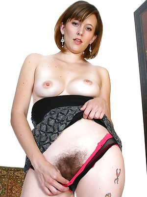 The ever so elegant Sasha lifts her dress seductively to show you her hairy pussy through her black and pink knickers. Its a bush so moist and pink that you can nearly taste it.