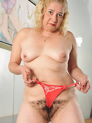 Slutty mature Leenuh does a nasty striptease and got her natural hairy pussy slammed in this porn story