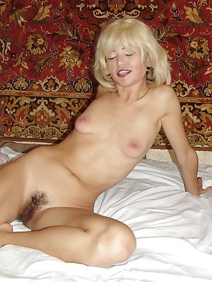 Naughty Asian wearing a blonde wig naked and playing with her bush covered pussy slit