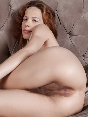 Natural redhead Mimi Lea removes her threads to display an extreme hairy muff