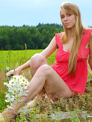 Young Euro girl holds a bunch of daisies while getting naked in farmer's field