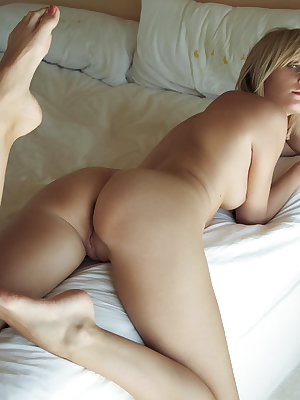 Erotic blonde bombshell Deni posing glamorously naked with beads on her bed