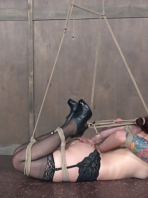 Tattooed slave Ariel Blue in nylons bound spreadeagled and gagged with tape
