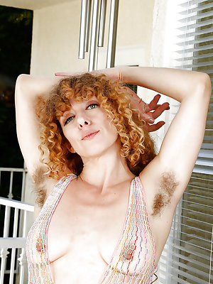 Hirsute natural redhead Leona spreading hairy pink pussy in bodystocking