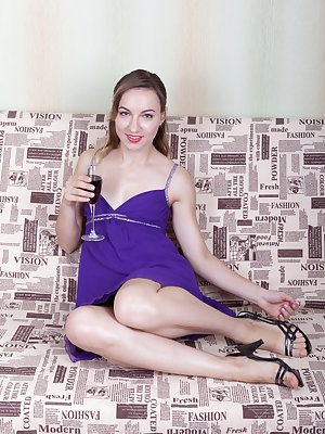 Yuliya is having beverage in her purple dress and strips naked feeling horny. She strips and shows us her hairy pussy and then grabs her vibrator. She then masturbates with it and orgasms loudly.