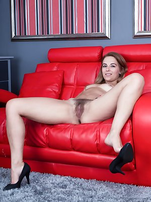 "Anna Smith poses on her red couch after stripping off her white blouse and grey skirt. All naked, she shows off her 5'5"" body, her hairy pussy and sexy body. She moves all over the couch to show and play."