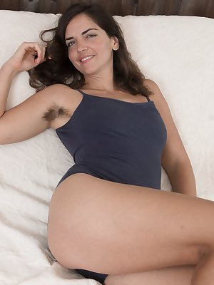 Katie Z is in bed, in her blue tights, and showing off her hairy pits and legs. She strips off the tights, and poses naked and we just admire her hairy pussy. It is full and rich, and invites us all in.