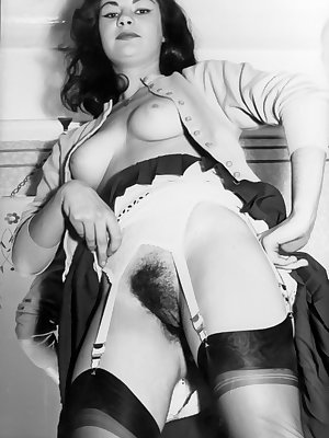 Dark haired vintage pornstar lifting her skirt to expose her hairy beaver