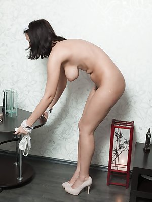 Brunette maid Ramira strips off uniform to show off her naturally hairy pussy