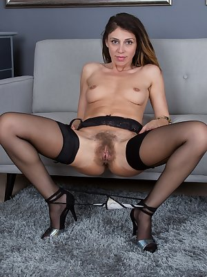 Chloe R is by her blue sofa and stripping off her lingerie and stockings. All naked, she spreads her legs and shows her hairy pussy and 34B natural breasts. She is quite lovely there.