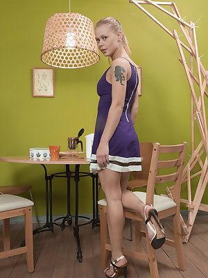 Darina Nikitina is eating cookies and takes off her purple dress and red panties after. She strips nude, climbs on her wooden table, and masturbates on the table, to orgasm and moan loudly.
