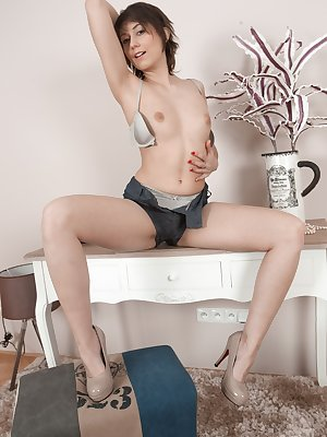 Meggie is by her boudoir table, and stripping naked feeling extra sexy. She strips nude, and shows us her very hairy pussy. She drags pearls over her bush and then touches her pink pussy more.