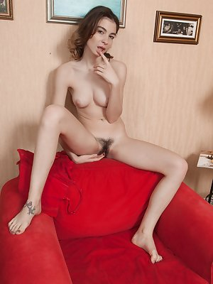 Taffy is on her red couch doing makeup and she loves to use the brush across her hairy pussy. She strips completely naked and begins to touch herself. She touches her hairy pussy with passion.